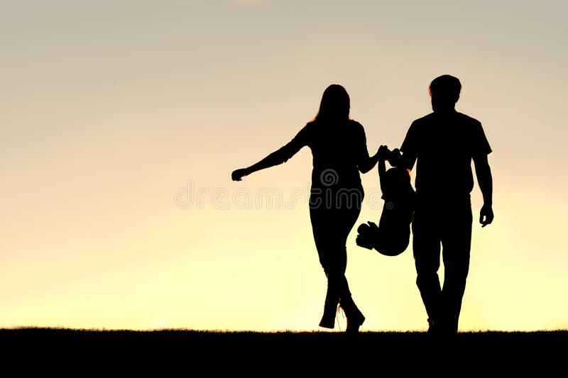 Silhouette of Family of Three People Walking at Sunset. A silhouette of a family of three people, including mother, father, and young child are playing around royalty free stock photo