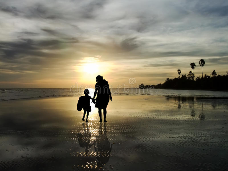 The silhouette of family watching the sunrise on the beach royalty free stock photography