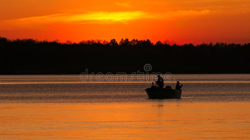 Silhouette of father and son fishing on lake at sunset stock images