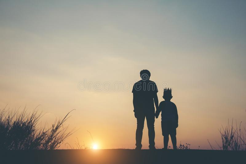 Silhouette of father and son standing. Together stock image