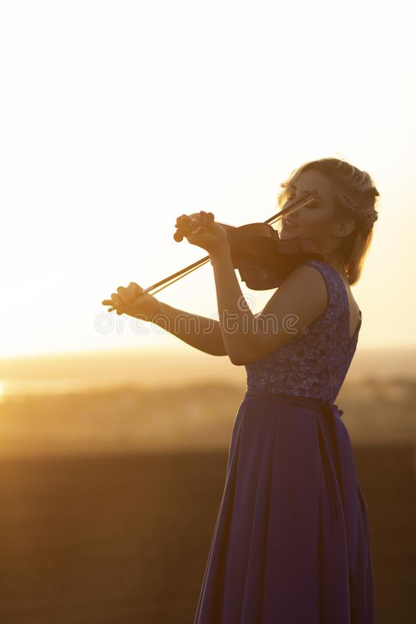 Silhouette of a female figure playing the vio and hobbylin at sunset, woman relaxing in music, performance on nature, concept art stock photos