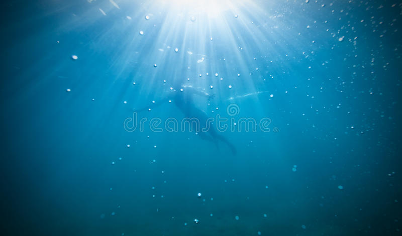 Silhouette of female freediver floating through royalty free stock image