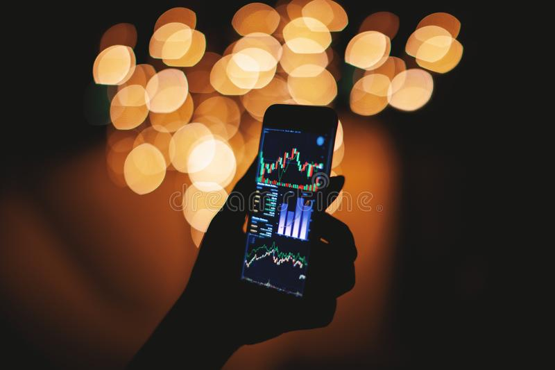 Silhouette female hand holding smart phone with stock trading display with light bokeh background. Silhouette of female hand holding smart phone in the dark with stock photo