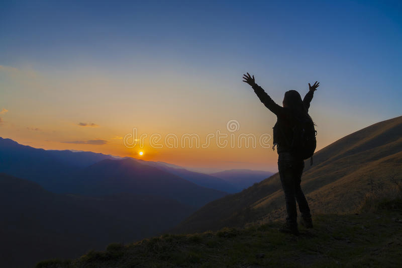 Silhouette of female hiker arms raised into sunset