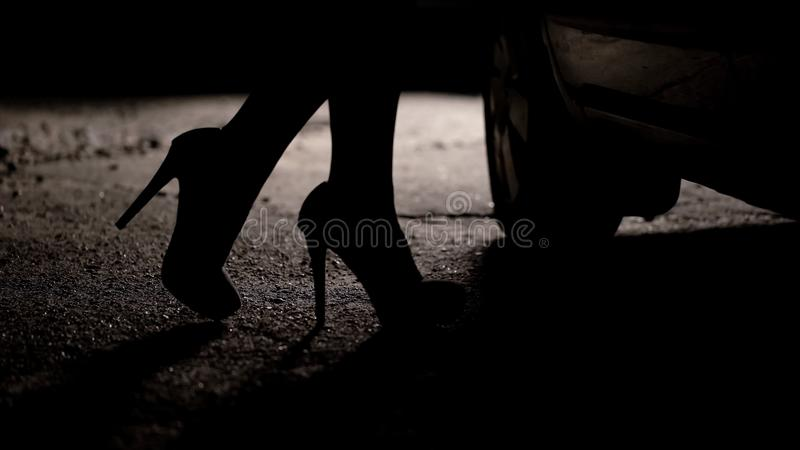 Silhouette of female legs in high heels coming to car, prostitution, sex tourism. Stock photo royalty free stock photos