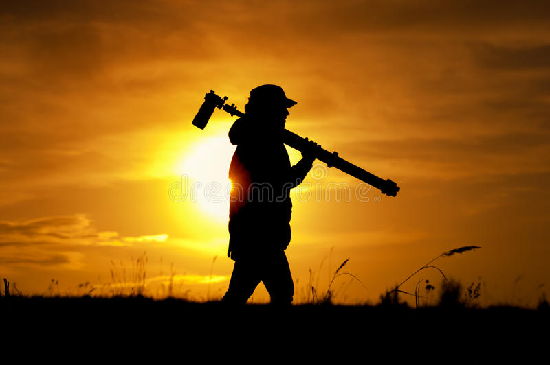 Silhouette of female photographer walking outdoors royalty free stock image