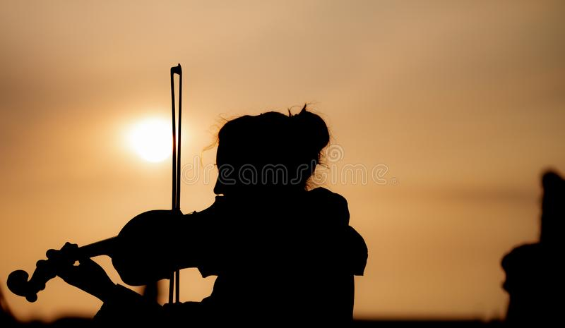 Silhouette of female playing the violin during sunset against the sun - Taken in Prague. A female plays on a stringed instrument to crowds of people in Prague stock photo