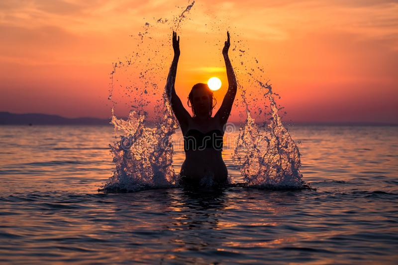 Silhouette of female splashing water with her hands at sunset over sea stock image