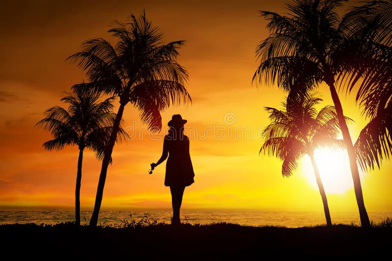 Silhouette of female tourist standing on the beach. At sunset stock photo