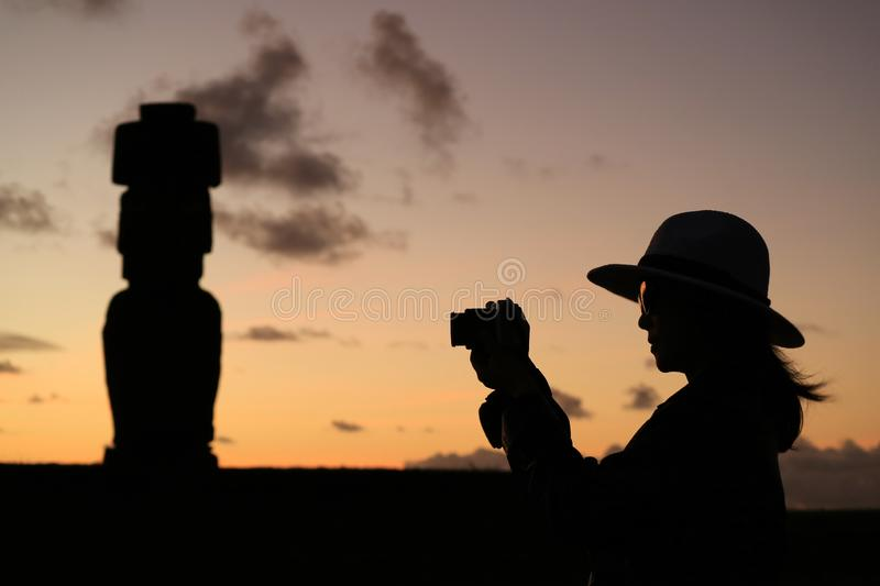 Silhouette of female tourist taking pictures of the famous Moai statue at Ahu Tahai archaeological site on Easter Island stock image