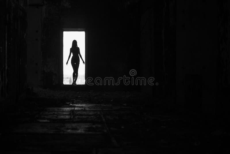 Silhouette femelle dans la photo noire et blanche de porte image stock