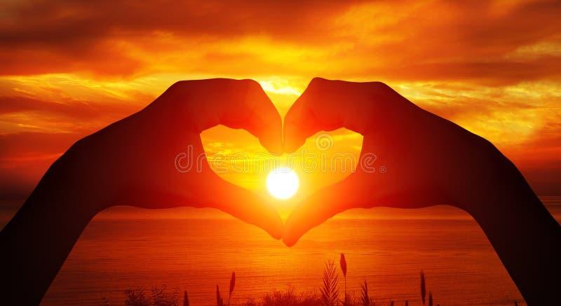 Silhouette femelle en forme de coeur de mains avec le fond de coucher du soleil images stock