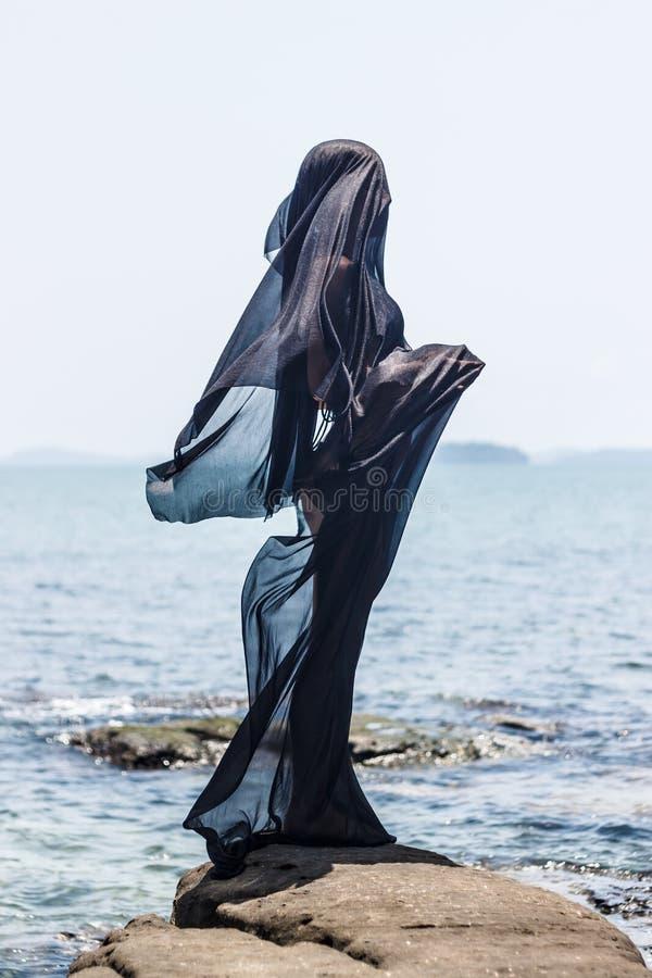 Silhouette femelle enveloppée dans le tissu noir posant au bord de la mer rocheux photographie stock
