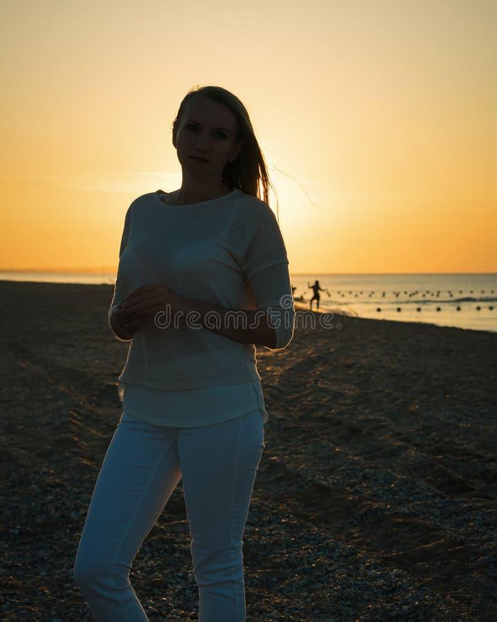 Silhouette femelle sur le fond de coucher du soleil, chiffre humain drôle image libre de droits