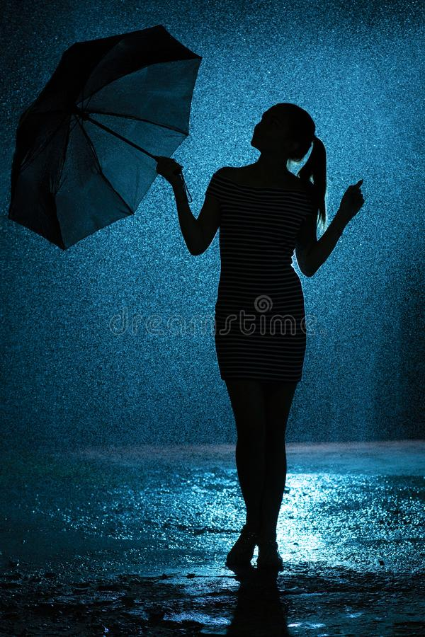 Silhouette of the figure of a young girl with an umbrella in the rain, a young woman is happy to drops of water, concept weather royalty free stock image