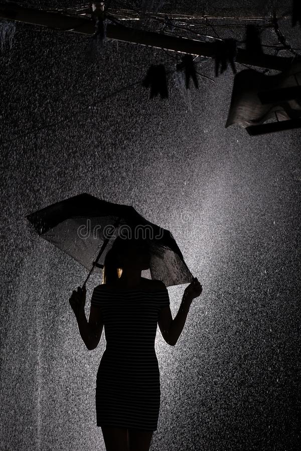 Silhouette of the figure of a young girl with an umbrella in the rain, a young woman profile. Black and white silhouette of the figure of a young girl with an stock images