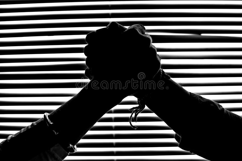 Silhouette figures in monochrome of hand shaking. And the background is a pattern of striped stripes of light and shadow and dark and lit areas for web design royalty free stock photo