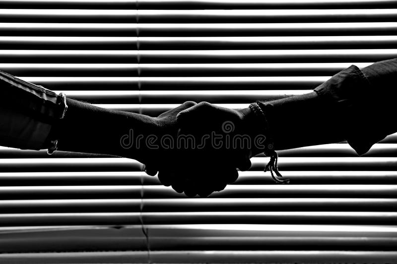 Silhouette figures in monochrome of hand shaking in dark light. Silhouette figures in monochrome of hand shaking and the background is a pattern of striped stock image