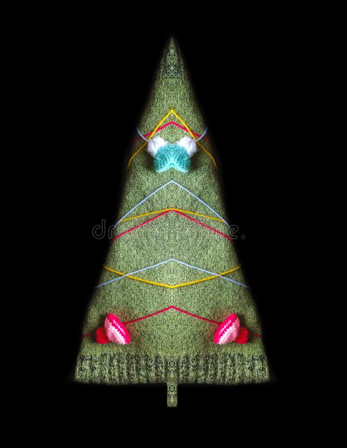 Silhouette of fir tree made of woolen cloth, colorful threads and knitted cap decor. Silhouette of Christmas tree made of woolen cloth, colorful threads and royalty free stock photo