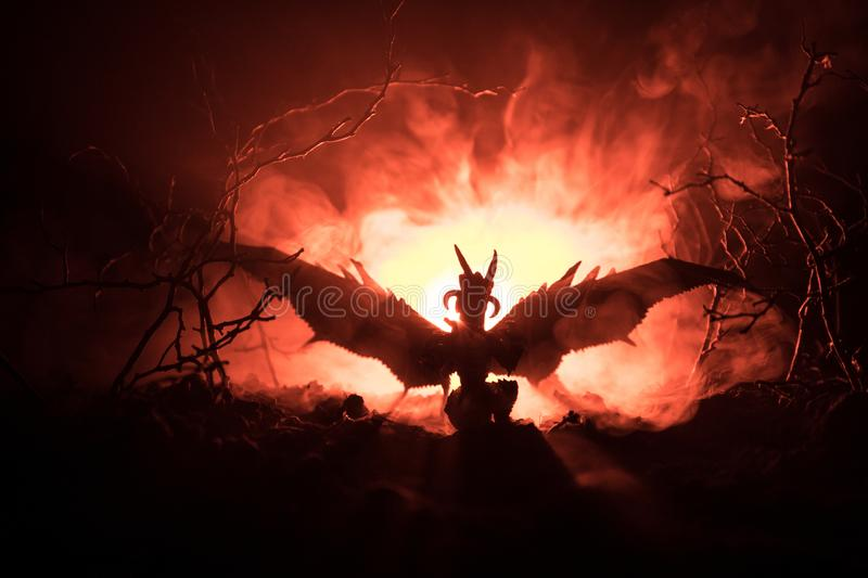 Silhouette of fire breathing dragon with big wings on a dark orange background. Horror image. Silhouette of fire breathing dragon with big wings on a dark orange royalty free stock photography