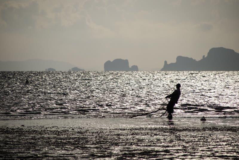 Silhouette fisherman on the beach stock photo
