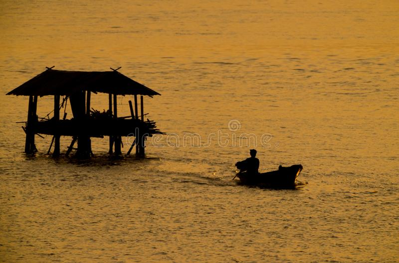 Silhouette of fisherman boat go out from fisherman`s cottage in river royalty free stock photography