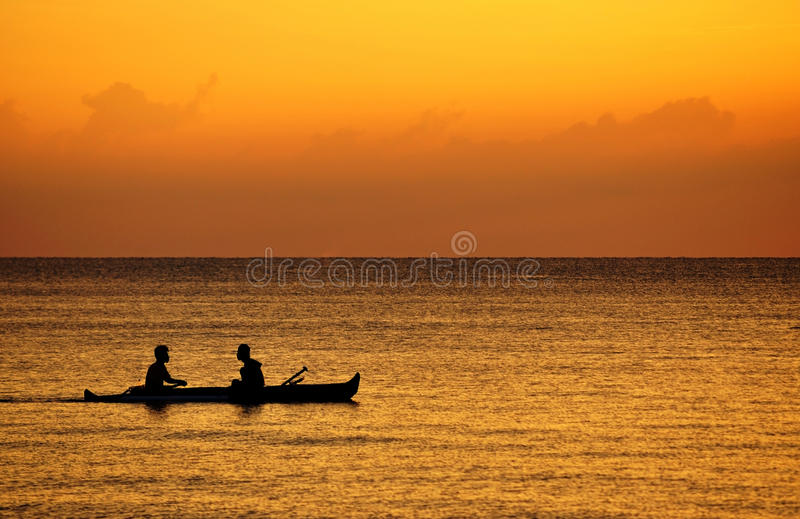 Silhouette of fisherman on a boat stock photo