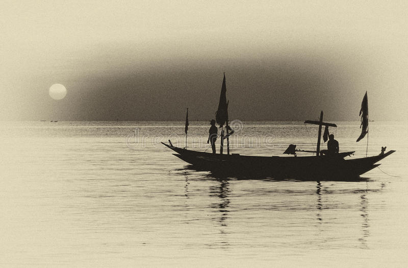 Silhouette of fisherman and boats floating at fore. Taken at Kenjeran beach, Surabaya, east Java, Indonesia royalty free stock photography