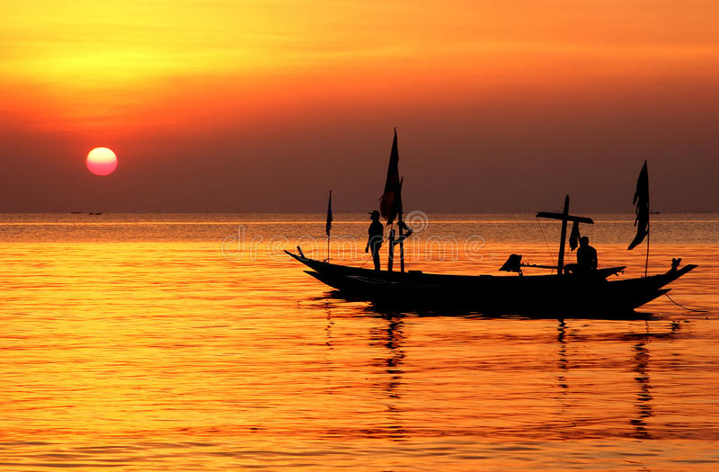 Silhouette of fisherman and boats floating at sea shore. Taken at Kenjeran beach, Surabaya, east Java, Indonesia royalty free stock photography