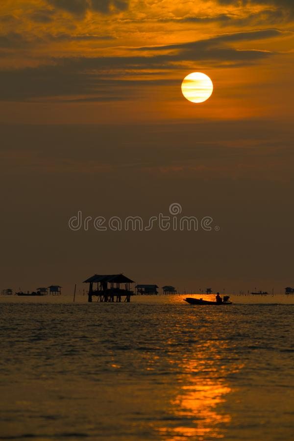 Silhouette of fisherman cottage and boatman in river on golden sunshine stock photography