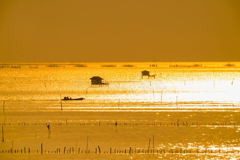 Silhouette of fisherman cottage and a boatman in river on golden sunshine royalty free stock images
