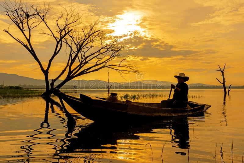 Silhouette fisherman on the fish boat on lake in the sunshine morning royalty free stock photo