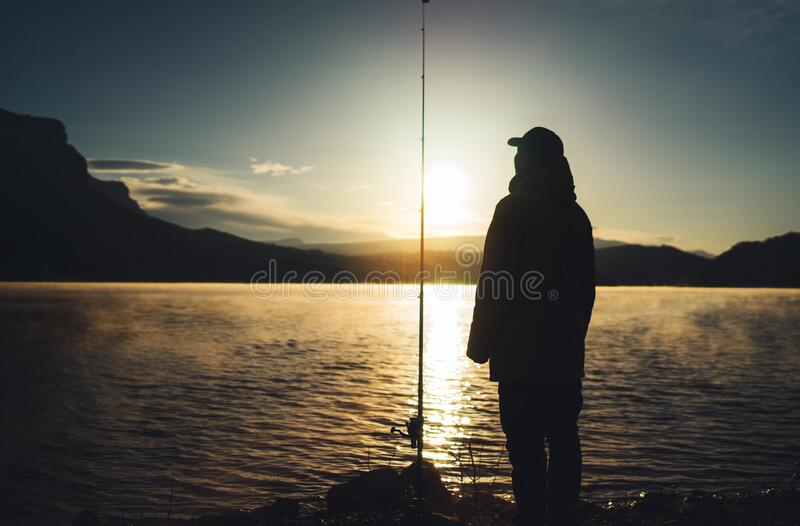 Silhouette fisherman with fishing rod at sunrise sunlight, man enjoy hobby sport on evening lake, outline person catch fish. At night sky, relax fishery concept royalty free stock photo