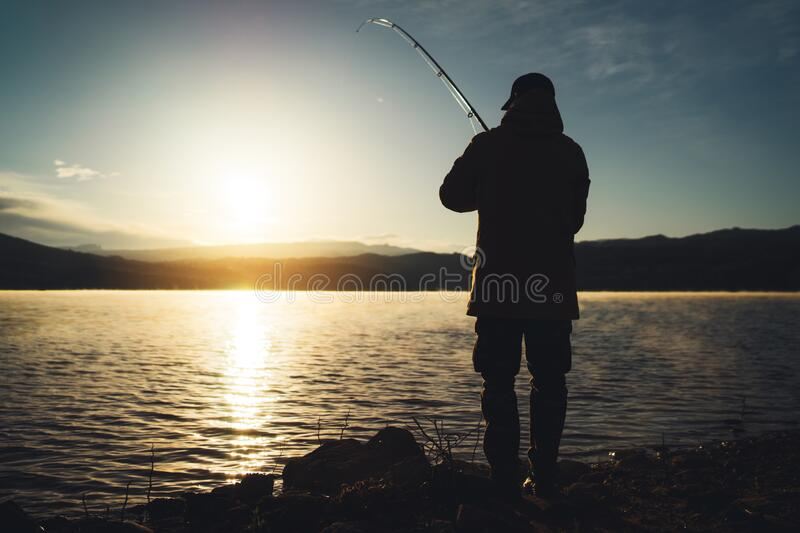 Silhouette fisherman with fishing rod at sunrise sunlight, outline man enjoy hobby sport on evening lake, person catch fish. At night sky, relaxation fishery royalty free stock photo