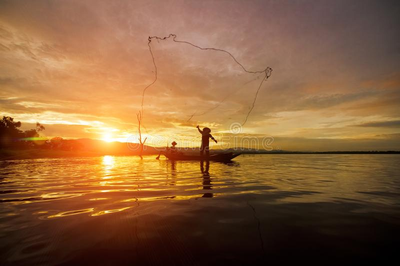 Silhouette Fisherman Fishing by using Net on the boat with sunshine in Thailand in the morning ,Nature and Culture concept stock photos