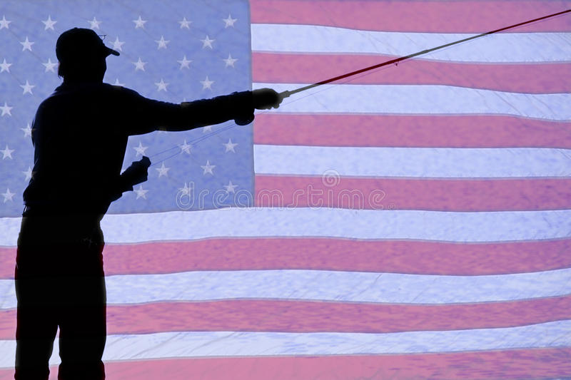 Silhouette of a Fisherman Holding a Fishing Pole. Fly fishing with a background of a USA American red white and blue flag royalty free stock photos