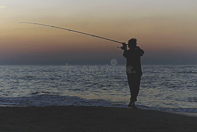 Silhouette of fisherman stock photos