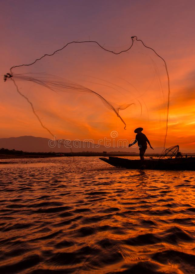 Silhouette fisherman with net at the lake in Thailand royalty free stock images