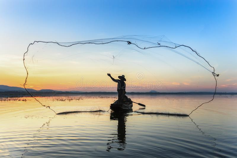 Silhouette of fisherman trowing the nets during sunset royalty free stock images