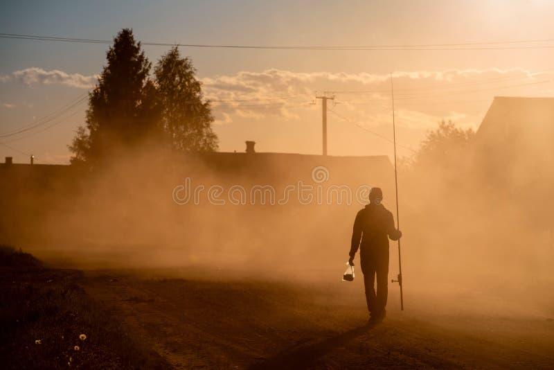 Silhouette of a fisherman walking along a dusty road stock image