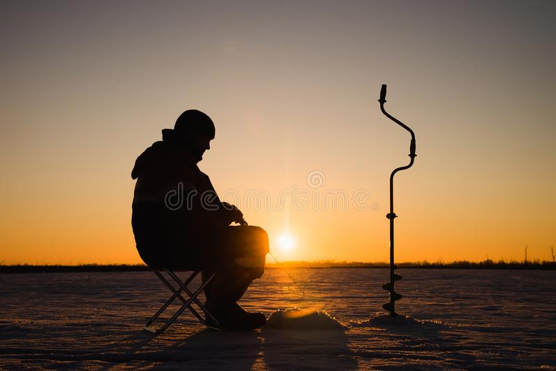 Silhouette of a fisherman on winter ice fishing at sunset. stock photos