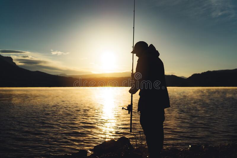 Silhouette fisherman wirh fishing rod at sunrise sunlight, outline man enjoy hobby sport on evening lake, person catch fish. On pond on background night sky stock photos