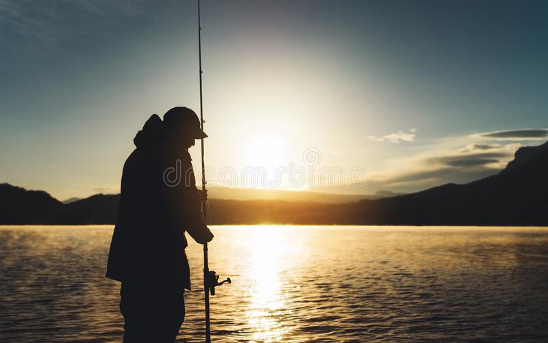 Silhouette fisherman wirh fishing rod at sunrise sunlight, outline man enjoy hobby sport on evening lake, person catch fish. Background night sky, relaxation royalty free stock image
