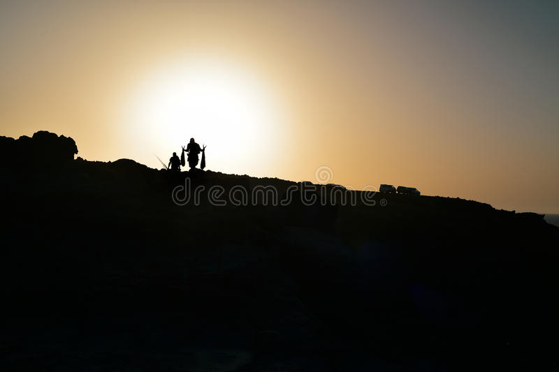 Silhouette of fishermen on a cliff at dusk royalty free stock photos