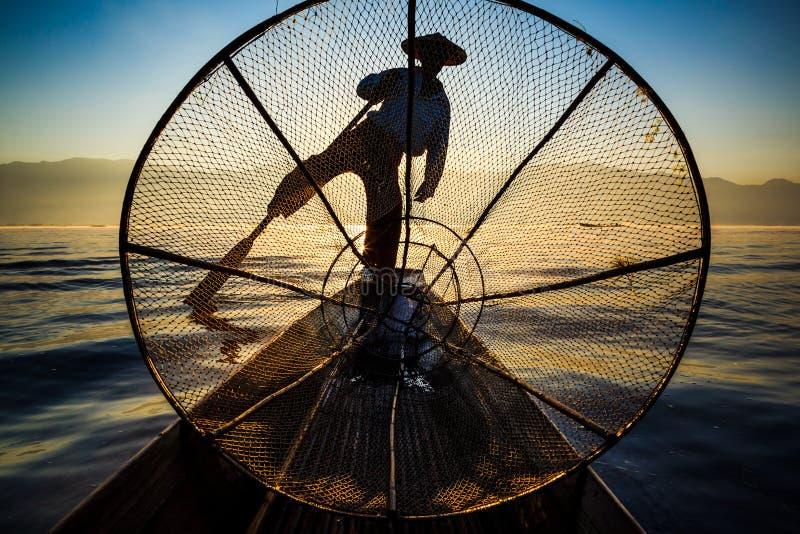 Silhouette fishermen in Inle Lake at sunrise, Myanmar royalty free stock photography