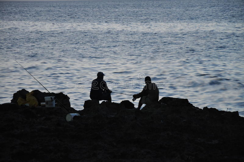 Silhouette of fishermen on rocks, Havana, Cuba. Silhouette of fishermen on rocks, Straits of Florida, Havana, Cuba royalty free stock photos