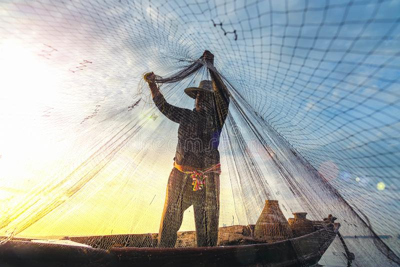Silhouette of fishermen using coop-like trap catching fish in lake with beautiful scenery of nature morning sunrise. Beautiful royalty free stock image