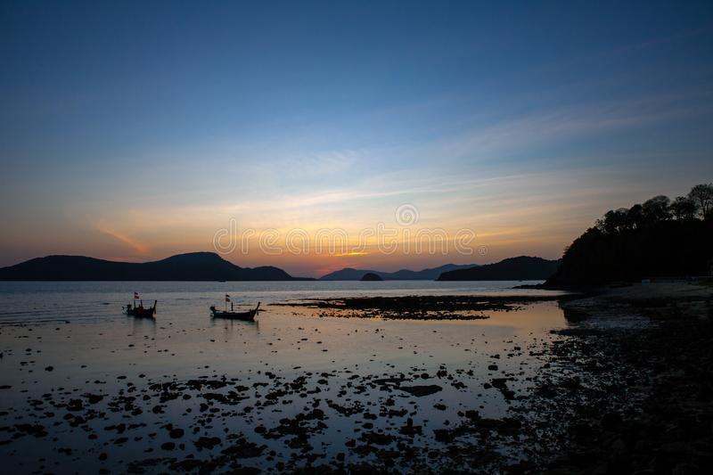 Silhouette of a fishing boat parked at the beach at sunset, dark blue tone At the sea, Krabi royalty free stock image