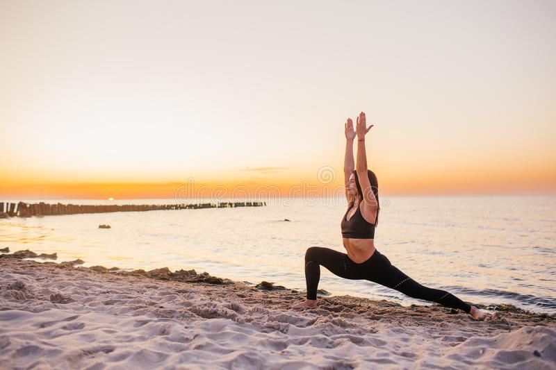 Silhouette of fitness athlete practicing warrior yoga pose meditating at beach sunset. Woman stretching doing morning meditation. Against colorful sky royalty free stock photography