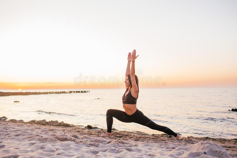 Silhouette of fitness athlete practicing warrior yoga pose meditating at beach sunset. Woman stretching doing morning meditation royalty free stock photos